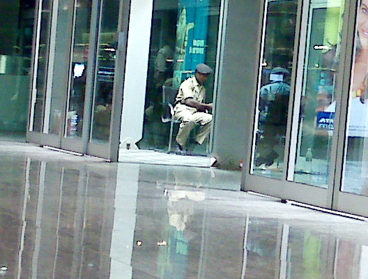 A security guard at Bangalore International Airport preparing tobacco instead of gaurading airport entrance